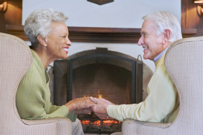 senior couple sitting by the fireplace